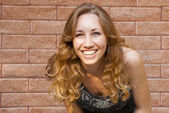 Photo of blonde girl with bright sincere smile on red brick back — Stock Photo