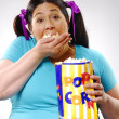 Fat young woman eating popcorn,young woman eating popcorn - 图库照片