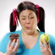 Fat girl holding a chocolate snack cake and apple,happy girl holding a chocolate snack cake and apple, — Stock Photo