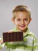 Little boy holding chocolate bar,Little boy eating chocolate — Stock Photo