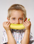One little kid holding a banana.Kid eating banana. — Stock Photo