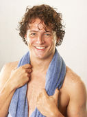 Young man and blue towel on white background. — Stock Photo
