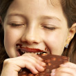Little girl eating chocolate. — Stock Photo #13772536