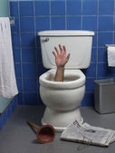 Hand reaches up through the seat from out of a toilet in a domestic bathroom. — Stock Photo