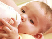 Mother is feeding her baby boy with a baby bottle — Stock Photo