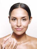 Latin woman applying makeup and lipstick — Stock Photo