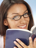Young latin woman reading with a book — Stock Photo