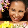 Hispanic young woman portrait with flowers. — Stock Photo #13815325