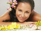 Hispanic young woman portrait with flowers. — Stock Photo