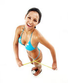 Young latin woman holding a measuring tape over a weight scale. — Stock Photo