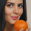Young woman holding a fresh orange — Stock Photo