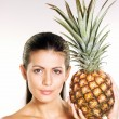 Young woman holding a pineapple on white background — Stock Photo