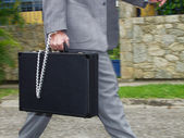 Businessman holding a handcuffs suitcase. — Stock Photo