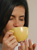 Beautiful young latin woman drinking a hot cup of drink — Stock Photo