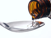 Pouring medicine syrup detail on a teaspoon — Stock Photo