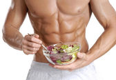Shaped and healthy body man holding a fresh salad bowl,shaped abdominal — Stock Photo