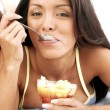 Young woman eating fresh fruit salad — Stock Photo #13878524