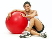 Young Woman doing fitness exercise with a red bal — Stock Photo