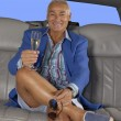 Royalty-Free Stock Photo: Happy senior man drinking champagne inside a limousine.
