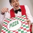 Pizza delivery man pointing at the pizza box — Stock Photo