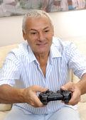 Senior man plays a computer game — Stock Photo