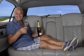 Happy senior man drinking champagne inside a limousine. — Stock Photo