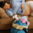 Pregnant woman laying on couch - Stock Photo