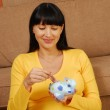Young and happy pregnant woman holding a piggy bank — Stock Photo #13990819