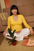 Jonge zwangere vrouw zittend op de vloer — Stockfoto