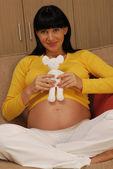 Pregnant woman holding a teddy bear — Stock Photo