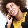 Stock Photo: Afro style young musing cell phone.