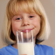 Stock Photo: Little girl holding a glass of milk