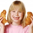 Little girl holding and eating croissant. — Stock Photo #14108926