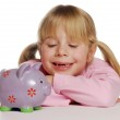 Little girl saving money using a piggy bank. — Stock Photo #14108974