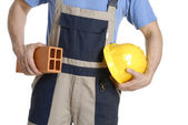 Construction worker holding a yellow helmet and brick. — Stock Photo