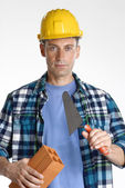 Construction man holding a wall brick and trowel on white background. — Stock Photo