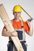 Worker holding wood boards and saw. — Stock Photo