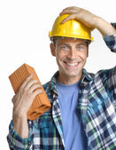 Construction man holding a wall brick on white background. — Stock Photo
