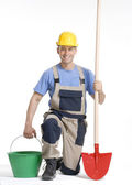 Worker holding a red bucket and shovel on white background. — Foto de Stock