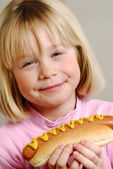 Little girl eating hot dog — Stock Photo