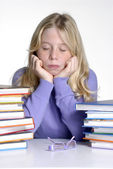 Exhausted school girl portrait behind books after studding. — Stock Photo