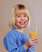 Little blonde girl behind an orange juice glass — Stock Photo