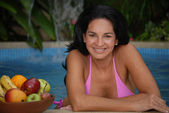 Hispanic woman and tropical fruits in a swimming pool. — Stock Photo
