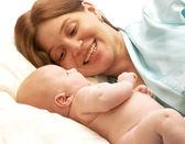 Spaanse moeder genieten van haar baby. moeder en pasgeboren genieten van in bed — Stockfoto