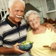 Happy senior couple preparing vegetable salad in the kitchen. Grandparents at kitchen preparing vegetable salad. — Stock Photo