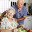 Happy senior couple preparing vegetable salad in the kitchen. Grandparents at kitchen preparing vegetable salad. — Stock Photo
