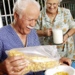 Stock Photo: Grandparents eating cereal corn flakes at kitchen.