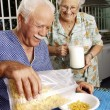 Grandparents eating cereal corn flakes at kitchen. — Stock Photo