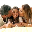 Stock Photo: Parents kissing their daughter in bed.