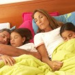 Stock Photo: Hispanic family sleeping together in bed.
